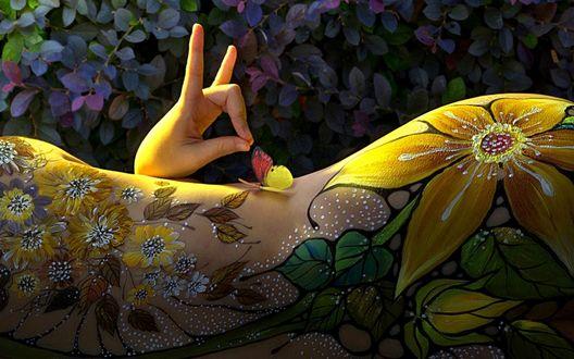 Обои Рука, сложенная в форму улитки, расположена возле бабочки, сидящей на разрисованном цветами женском теле