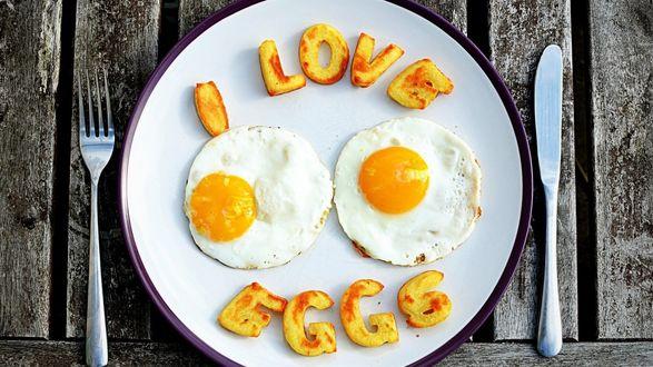 Обои Аппетитная глазунья на тарелке с надписью Я люблю яичницу, рядом вилка и нож на фоне досок