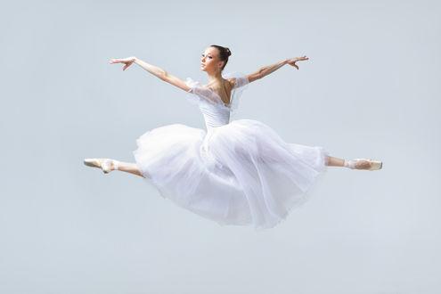 Обои Балерина в белом платье делает шпагат в прыжке
