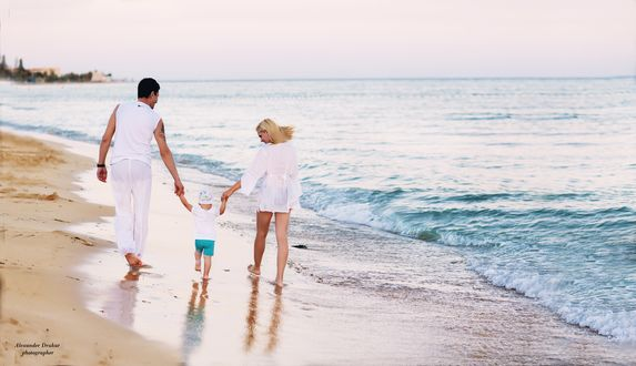 Обои Мужчина, ребенок и молодая женщина идут вдоль берега моря держась за руки. Фотограф Александр Друкар