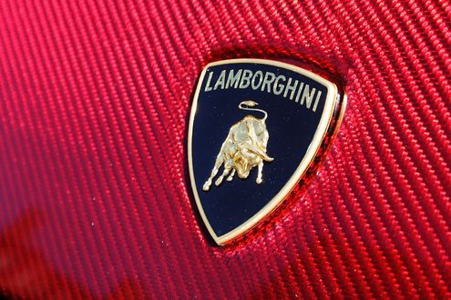 Обои Логотип Lamborgini на карбоновом капоте авто