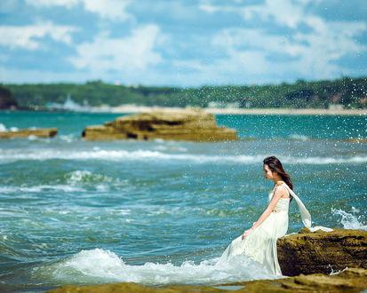 Обои Девушка азиатка в белом платье сидит на камне, у моря