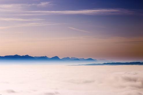 Обои Горные вершины над облаками на фоне неба
