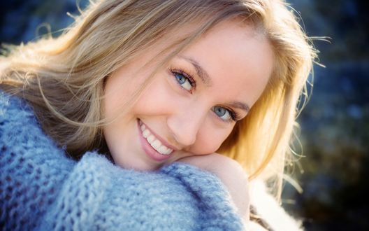 Обои Девушка с голубыми глазами улыбается и смотрит в камеру