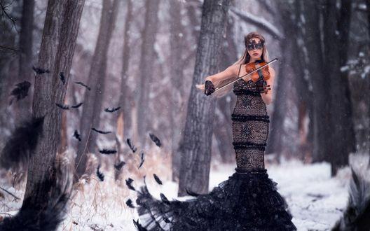 Обои Девушка со скрипкой в маске стоит в заснеженном лесу