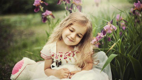 Обои Девочка с кроликом в руках сидит у цветов ириса
