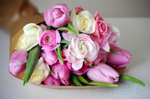 Обои Букет из роз, тюльпанов и пионов в бумажной обертке лежит на сером фоне