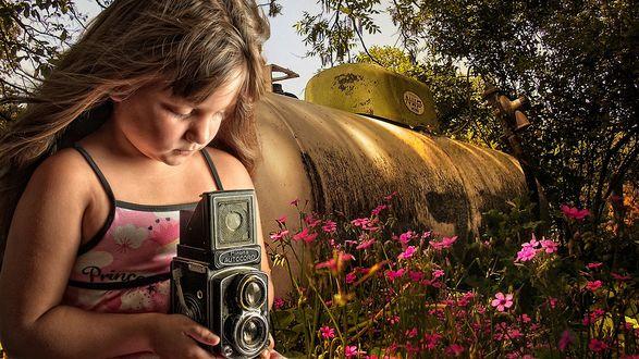 Обои Девочка держа в руках фотоаппарат фотографирует природу, стоя у огромной металлической бочки