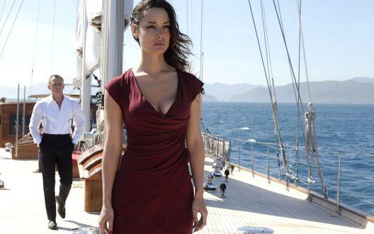 Обои На палубе судна стоит девушка в темно-красном платье, за ней виден Дэниел Крэйг (Daniel Craig) в роли Джеймса Бонда (James Bond), кадр из фильма Агент 007