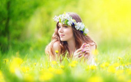 Обои Улыбающаяся девушка шатенка с длинными волосами в венке из белых цветов лежит на лугу среди цветов и смотрит в сторону