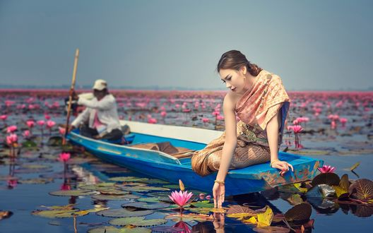 Обои Девушка сидит на краю лодки опустив руку в воду