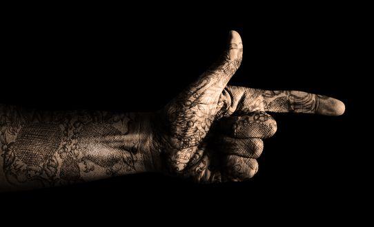 Обои Mano con tatuaje en un fondo negro / Рука с татуировкой на черном фоне