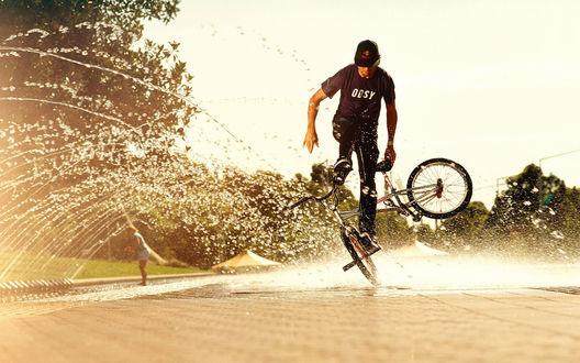 Обои Парень крутит финты на велосипеде, от колес летят брызги лужи