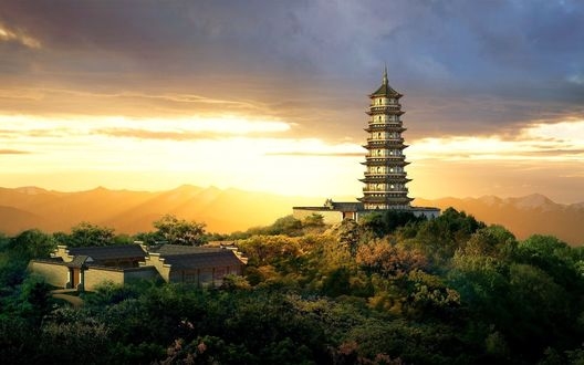 Обои Пагода стоит на холме на фоне заката, возле маленькая деревушка