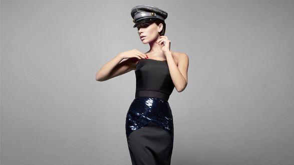 Обои Певица Victoria Beckham в фуражке позирует на сером фоне