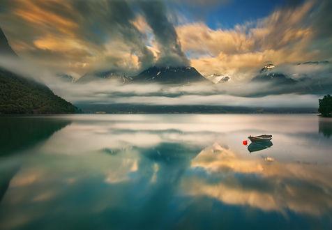 Обои Лодка дрейфует на воде под облачным небом, фотограф Krzysztof Browko