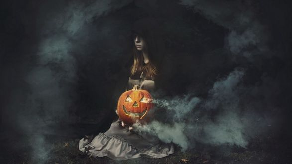 Обои Девушка в капюшоне сидит на траве с тыквой Хэллоуин на коленях