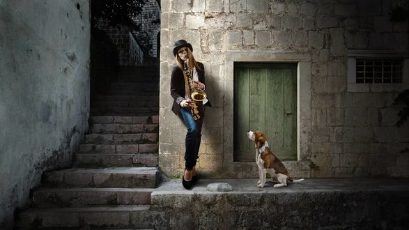 Обои Собака слушает игру девушки на саксофоне в подворотне