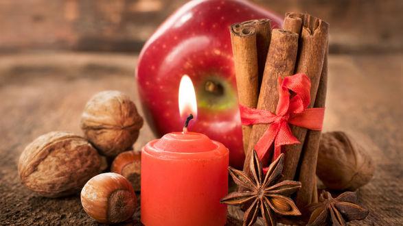 Обои Праздник Новый год, Рождество. Стол украшают яблоком, свечкой, ванилью перевязанной красной ленточкой, грецкими и лесными орехами