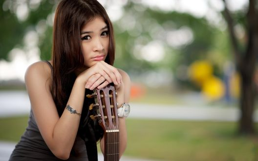 Обои Молоденькая китаяночка, грустит в парке, сидит на скамейке, облокотившись немного руками на гитару