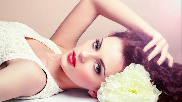 Обои Красивая брюнетка лежит на полу в красивом платье с цветком в волосах