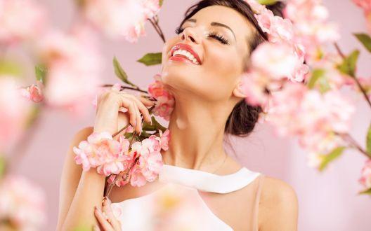 Обои Счастливая брюнетка в белом платье среди цветущих нежно-розовым цветом деревьев. Фон розовый
