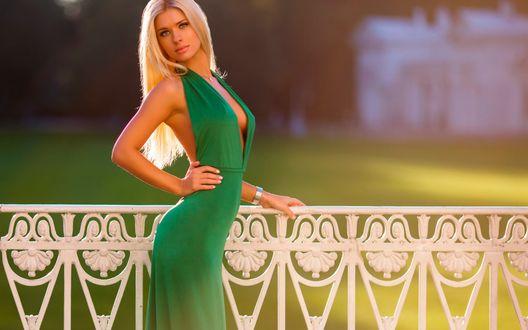 Обои Красивая блондинка, в зеленом открытом платье, стоит у забора на фоне дома и зеленого газона