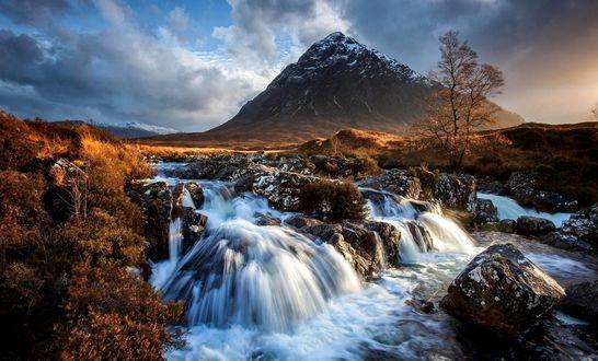 Обои Горный ручей бежит по камням, омывая их водой, среди равнины на фоне большой горы и неба с облаками