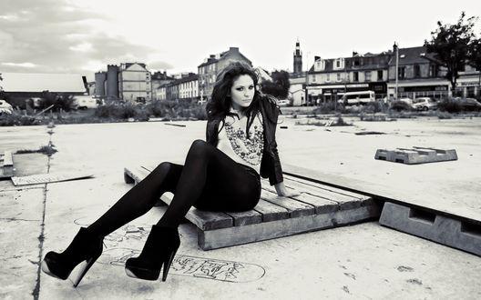 Обои Красивая Брюнетка сидит на досках на фоне города