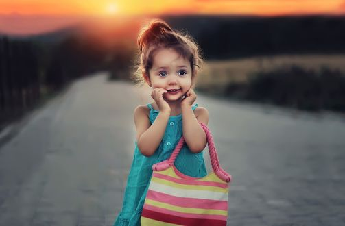 Обои Маленькая, радостная девочка с полосатой сумкой, стоит на дороге на размытом фоне
