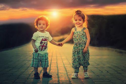 Обои Два милых ребенка, держась за руки, стоят на брусчатой дорожке на размытом фоне