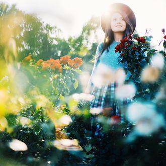 Обои Улыбающаяся девушка в шляпе стоит рядом с кустами роз, из-за спины ее освещают солнечные лучи, фотограф Ксения Засецкая