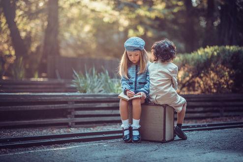 Обои Двое детей, мальчик и девочка сидят на чемодане, девочка, положив блокнот на коленки, что-то в нем пишет