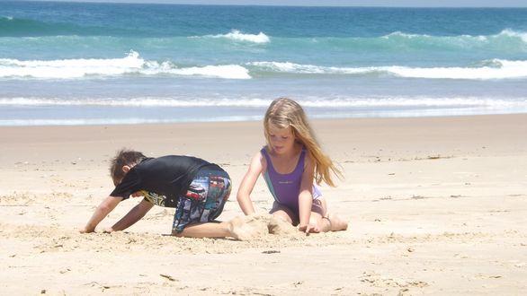 Обои Дети на пляже, строят замок из песка на фоне моря