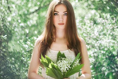 Обои Красивая девушка, в белом ажурном платье, с букетом ландышей в руках, на размытом фоне зелени деревьев