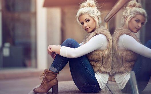 Обои Белокурая красотка в джинсах и жилетке из меха, сидит, обхватив руками коленки ног на фоне дома