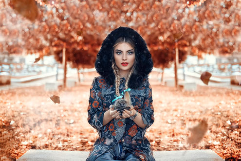 Обои Красивая девушка с косичками, сидит на фоне осенних деревьев и держит ежика в руках