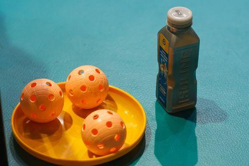 Обои Желтые мячики для флорбола, лежат в пластиковой тарелке, рядом с бутылкой