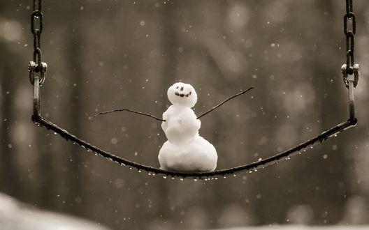 Обои Маленький снеговичок, стоит на детской качели под мокрым снегом, на качели капельки воды