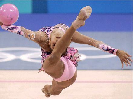 Обои Известная российская гимнастка Ольга Капранова выполняет прыжок прогнувшись с мячом