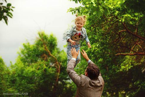 Обои Отец играет с дочкой подкидывая ее вверх на фоне деревьев, фотограф Максим Николаев