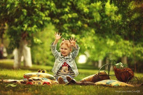 Обои Рыжеволосая, улыбающаяся девочка сидит на траве подняв руки вверх, рядом лежат подушки, игрушечная машинка, солнцезащитные очки и корзинка с цветами в виде велосипеда, фотограф Максим Николаев