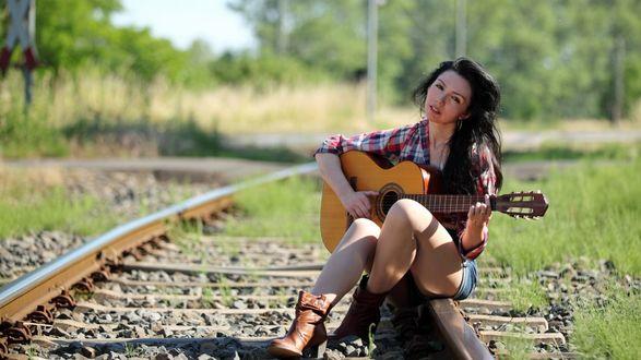 Обои Романтика железной дороги. Девушка с гитарой сидит на рельсах железнодорожных путей сообщений