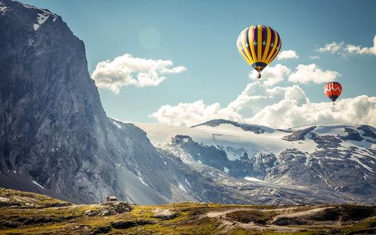 Обои Воздушные шары летят над деревушкой у подножья гор
