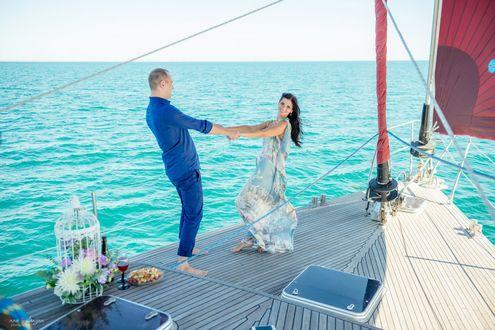 Обои Девушка и мужчина, держась за руки, стоят на палубе яхты, которая вышла в море, рядом с ними цветы, бокалы с вином и еда, фотограф Анна Асланян