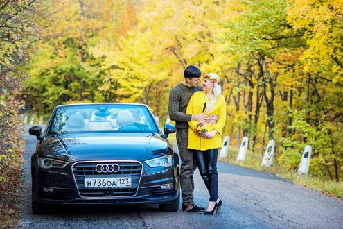 Обои Парень и девушка с венком на голове стоят обнявшись у авто на дороге, вокруг которой растут деревья с желтыми листьями, фотограф Анна Асланян
