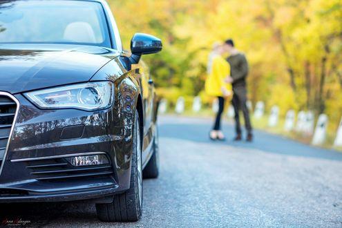 Обои Автомобиль стоит на дороге, невдалеке на размытом фоне стоят целующиеся парень и девушка, фотограф Анна Асланян