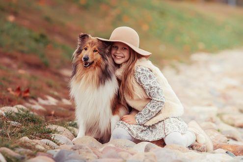 Обои Улыбающаяся девочка в шляпе сидит среди камней, обняв собаку породы колли, фотограф Марина Полянская