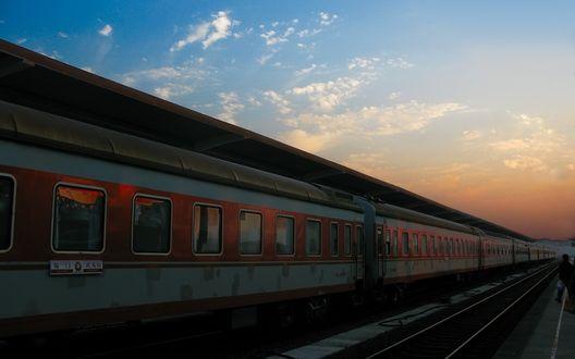 Обои Старый состав поезда на вокзале на фоне облаков озаряемых закатом