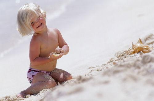 Обои Маленький мальчик, играет на морском берегу с ракушками, мальчик очень довольный